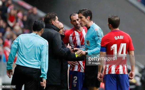 Head coach Diego Pablo Simeone of Atletico Madrid speaks with Referee Munuera Montero during the La Liga match between Atletico Madrid and Getafe at...