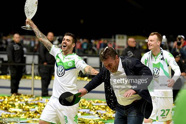 Head coach Dieter Hecking of VfL Wolfsburg receives a beer shower from Vieirinha after his teams victory in the DFB Cup Final match between Borussia...