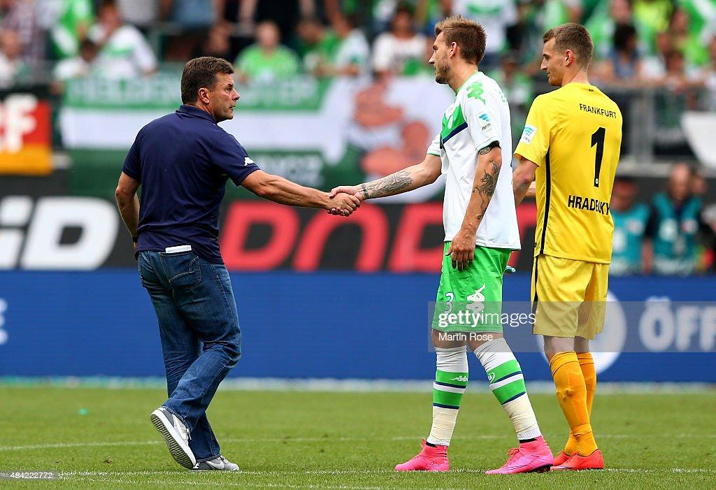 Head coach Dieter Hecking shakes hands with Nicklas Bendtner of VfL Wolfsburg after winning the Bundesliga match between VfL Wolfsburg and Eintracht Frankfurt at Volkswagen Arena on August 16, 2015 in Wolfsburg, Germany.