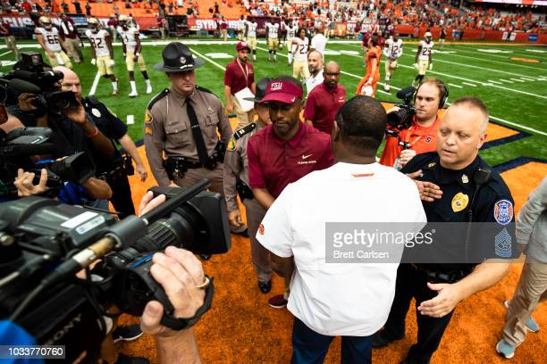 Head coach Dino Babers of the Syracuse Orange and head coach Willie Taggart of the Florida State Seminoles shake hands after the game at the Carrier...