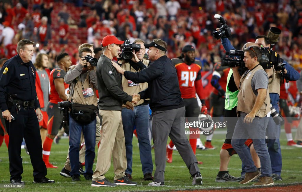 Head coach Dirk Koetter of the Tampa Bay Buccaneers meets up on the field with head coach Sean Payton of the New Orleans Saints following the Buccaneers' 31-24 win at an NFL football game on December 31, 2017 at Raymond James Stadium in Tampa, Florida.