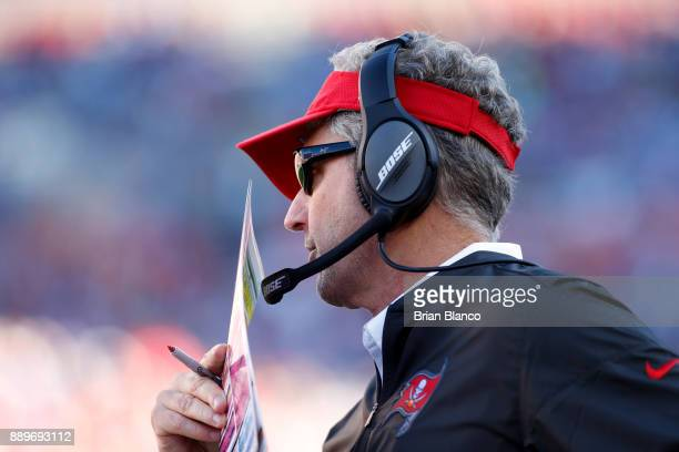 Head coach Dirk Koetter of the Tampa Bay Buccaneers speaks into his headset on the sidelines during the fourth quarter of an NFL football game...