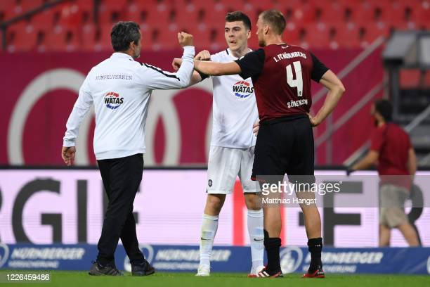 Head coach Dirk Schuster of Aue bumps elbows with Jacob Rasmussen of Aue and Asger Sorensen of Nuernberg during the Second Bundesliga match between...