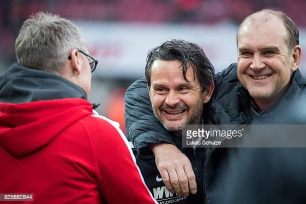 Head Coach Dirk Schuster of Augsburg Head Coach Peter Stoeger of Koeln and Joerg Schmadtke of Koeln are seen prior to the Bundesliga match between 1...