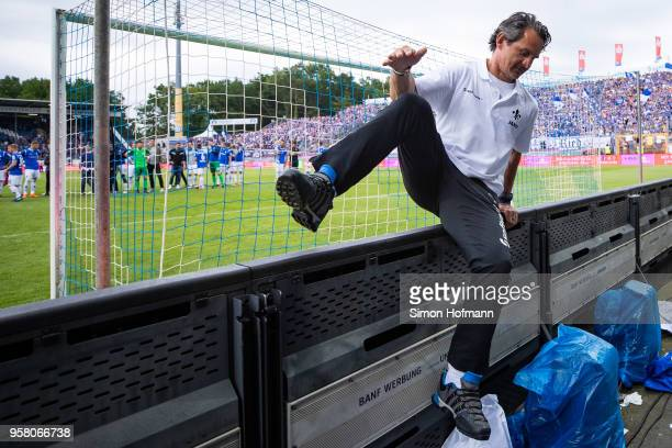 Head coach Dirk Schuster of Darmstadt jumps over the advertising board to celebrate winning with supporters after the Second Bundesliga match between...