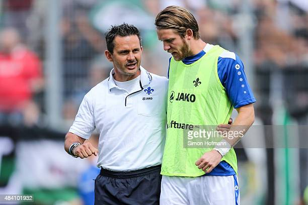 Head coach Dirk Schuster of Darmstadt talks to Peter Niemeyer prior to the Bundesliga match between SV Darmstadt 98 and Hannover 96 at MerckStadion...