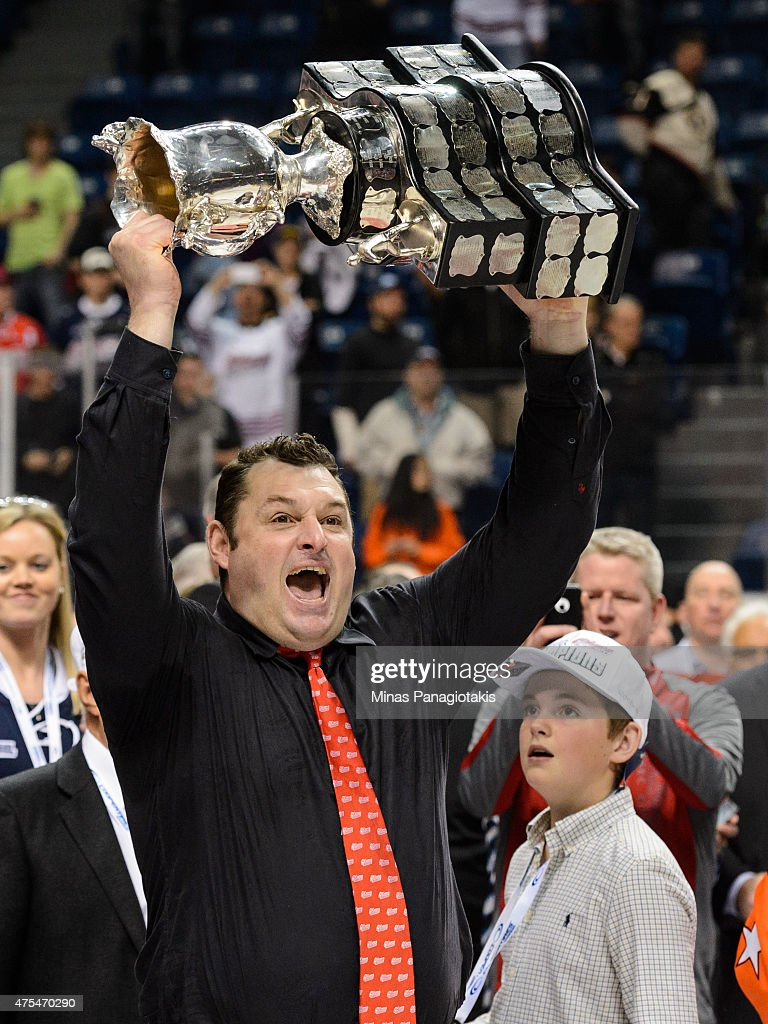 Head coach DJ Smith of the Oshawa Generals hoists the Memorial Cup in the air after his team defeated the Kelowna Rockets during the 2015 Memorial Cup Championship at the Pepsi Coliseum on May 31, 2015 in Quebec City, Quebec, Canada. The Oshawa Generals defeated the Kelowna Rockets 2-1 in overtime and become the 2015 Memorial Cup Champions.