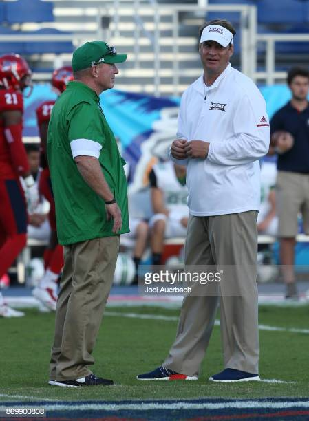 Head coach Doc Holliday of the Marshall Thundering Herd and Head coach Lane Kiffin of the Florida Atlantic Owls talk at midfield prior to the game at...