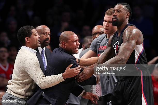 Head coach Doc Rivers of the Los Angeles Clippers is held back by DeAndre Jordan and Blake Griffin after a technical foul call against the Brooklyn...