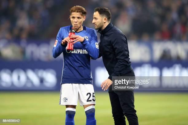 Head coach Domenico Tedesco of Schalke speaks to Amine Harit of Schalke during the Bundesliga match between FC Schalke 04 and 1 FC Koeln at...