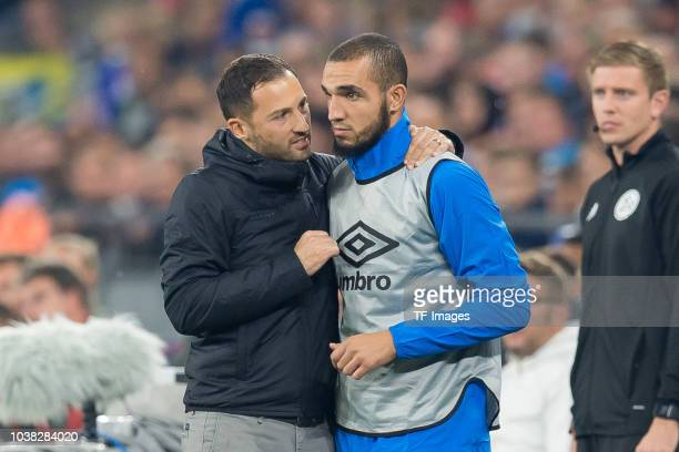 Head coach Domenico Tedesco of Schalke speaks with Nabil Bentaleb of Schalke during the Bundesliga match between FC Schalke 04 and FC Bayern Muenchen...