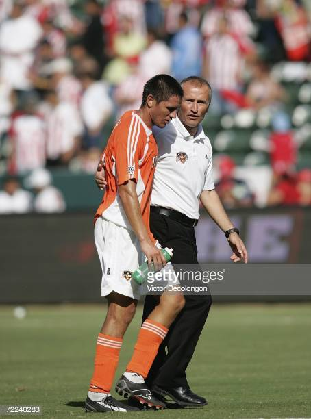 Head Coach Dominic Kinnear of the Houston Dynamo has a word with his player Brian Ching after they lost to Chivas USA 21 in the first game of their...