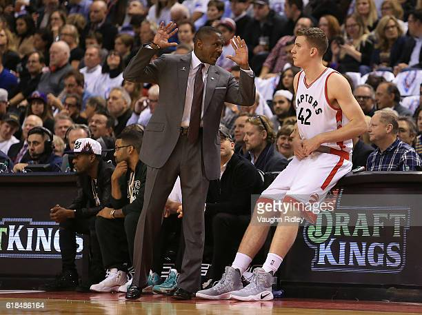 Head coach Dwane Casey of the Toronto Raptors talks to Jakob Poeltl before he makes his debut during the first half of an NBA game against the...