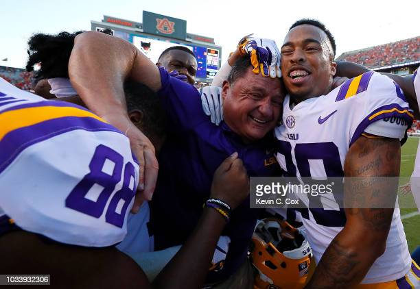 Head coach Ed Orgeron celebrates with Mannie Netherly and Jacory Washington after their 2221 win over the Auburn Tigers at JordanHare Stadium on...