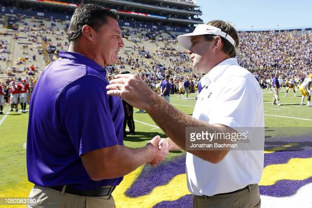 Head coach Ed Orgeron of the LSU Tigers and head coach Kirby Smart of the Georgia Bulldogs meet on the field before a game at Tiger Stadium on...