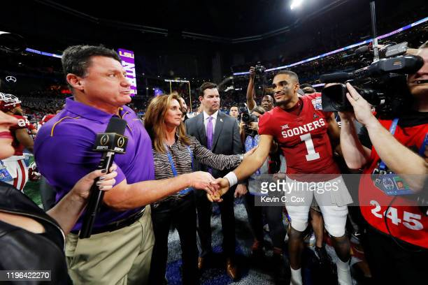 Head coach Ed Orgeron of the LSU Tigers and quarterback Jalen Hurts of the Oklahoma Sooners shake hands after LSU Tigers wins the Chick-fil-A Peach...