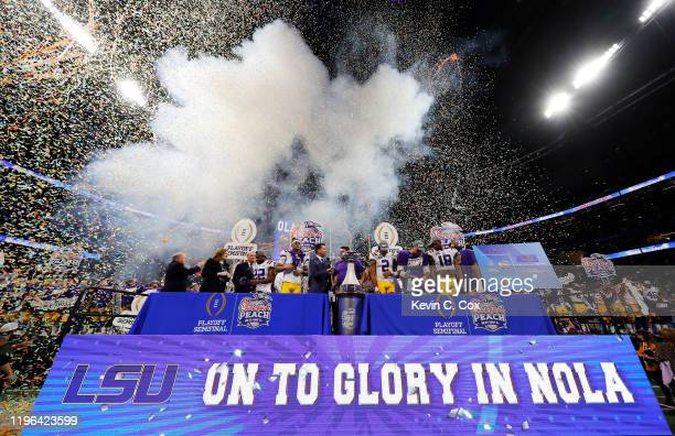 Head coach Ed Orgeron of the LSU Tigers and team celebrate on the podium after winning 28-63 over the Oklahoma Sooners in the Chick-fil-A Peach Bowl...