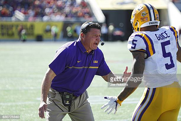 Head coach Ed Orgeron of the LSU Tigers congratulates Derrius Guice after his one-yard touchdown reception against the Louisville Cardinals in the...