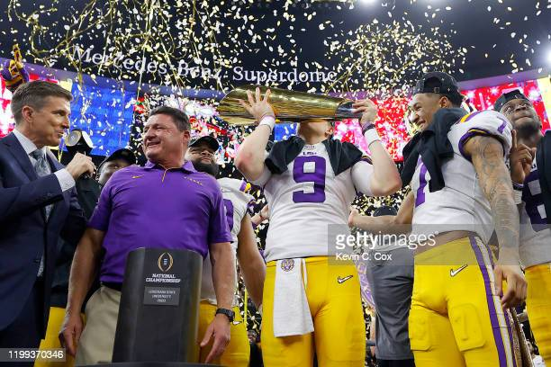 Head coach Ed Orgeron of the LSU Tigers Joe Burrow of the LSU Tigers and Grant Delpit of the LSU Tigers celebrate with the trophy after defeating the...