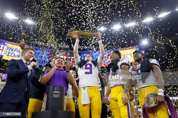 Head coach Ed Orgeron of the LSU Tigers, Joe Burrow of the LSU Tigers and Grant Delpit of the LSU Tigers celebrate with the trophy after defeating...