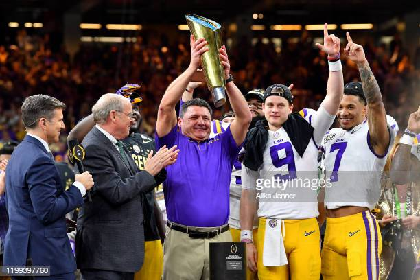 Head coach Ed Orgeron of the LSU Tigers raises the National Championship Trophy with Joe Burrow and Grant Delpit after the College Football Playoff...