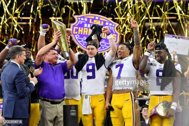 Head coach Ed Orgeron of the LSU Tigers raises the National Championship Trophy with Joe Burrow Grant Delpit and Patrick Queen after the College...