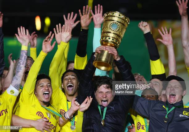 Head coach Edin Terzic and players of Borussia Dortmund celebrate with the trophy after winning the DFB Cup final match between RB Leipzig and...