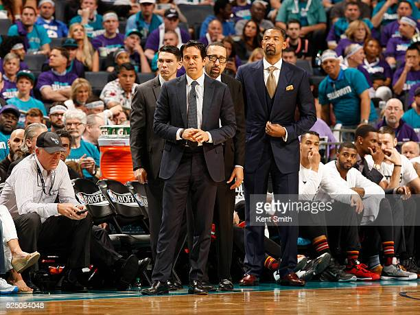 Head Coach Erik Spoelstra and coaches of the Miami Heat looks on against the Charlotte Hornets during Game Four of the Eastern Conference...