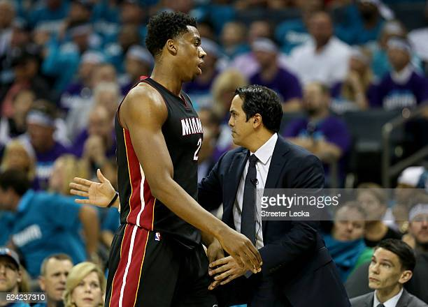 Head coach Erik Spoelstra stands with his player Hassan Whiteside of the Miami Heat against the Charlotte Hornets during game four of the Eastern...