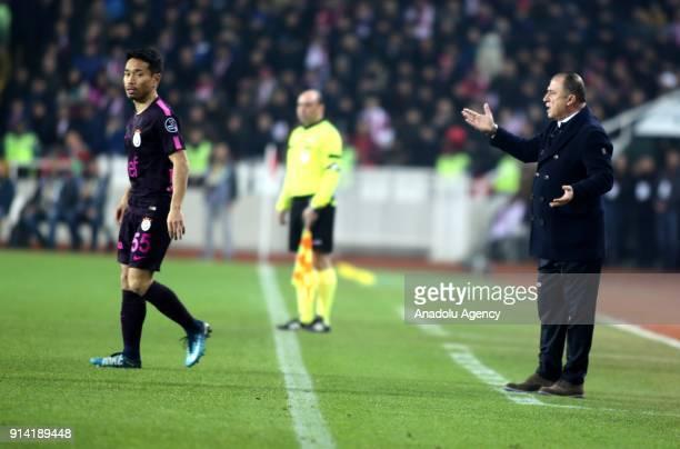 Head coach Fatih Terim of Galatasaray gives tactics to his team's player Yuto Nagatomo during a Turkish Super Lig week 20 soccer match between Demir...