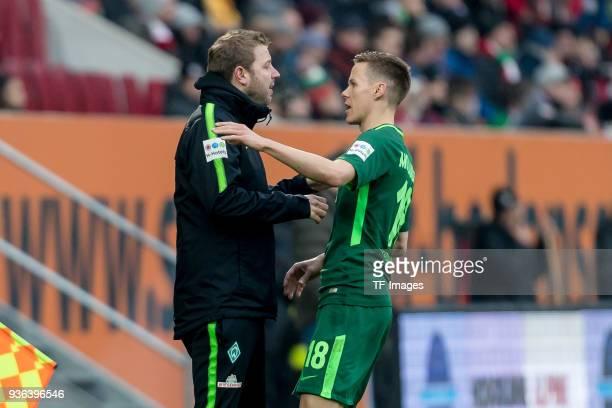 Head coach Florian Kohfeldt of Bremen speaks with Niklas Moisander of Bremen during the Bundesliga match between FC Augsburg and SV Werder Bremen at...