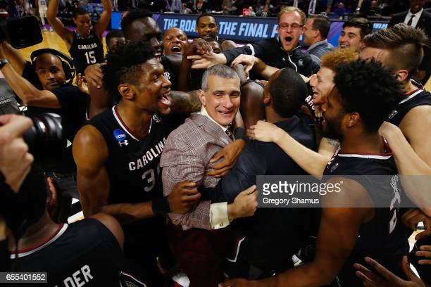 Head coach Frank Martin of the South Carolina Gamecocks celebrates with players after defeating the Duke Blue Devils 8881 in the second round of the...