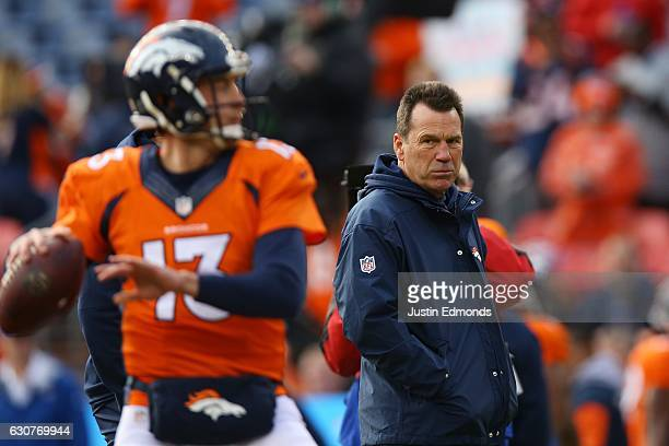 Head coach Gary Kubiak of the Denver Broncos watches Trevor Siemian warm up before the game against the Oakland Raiders at Sports Authority Field at...