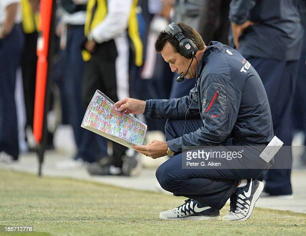 Head coach Gary Kubiak of the Houston Texans looks at a play chart against the Kansas City Chiefs during the second half on October 20 2013 at...
