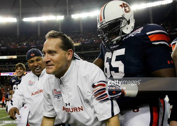 Head coach Gene Chizik of the Auburn Tigers celebrates after their 43-24 win over the Virginia Cavaliers with Tunde Fariyike and Trooper Taylor...