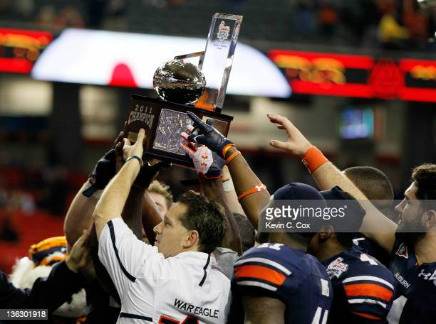 Head coach Gene Chizik of the Auburn Tigers celebrates with the trophy after their 43-24 win over the Virginia Cavaliers during the 2011 Chick Fil-A...
