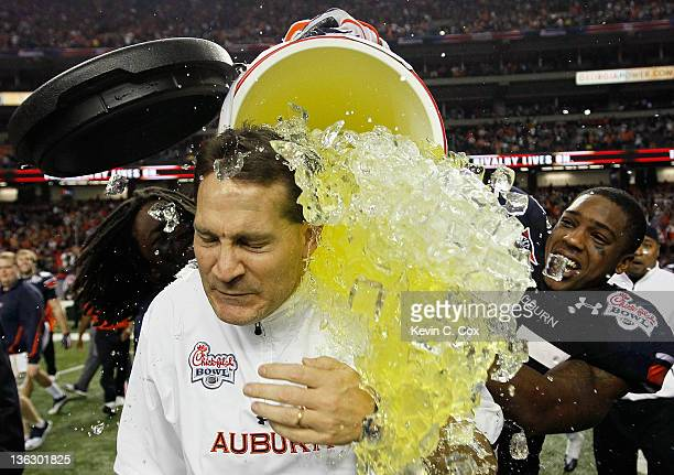 Head coach Gene Chizik of the Auburn Tigers is dunked after their 43-24 win over the Virginia Cavaliers during the 2011 Chick Fil-A Bowl at Georgia...