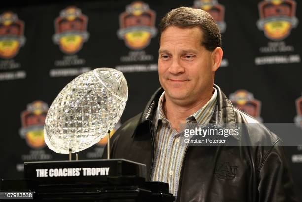 Head coach Gene Chizik of the Auburn Tigers poses with the Coaches trophys during a press conference for the Tostitos BCS National Championship Game...