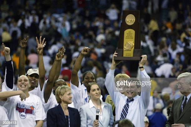 Head coach Geno Auriea of the University of Connecticut Huskies hoists the NCAA Women's Championship trophy after defeating the University of...