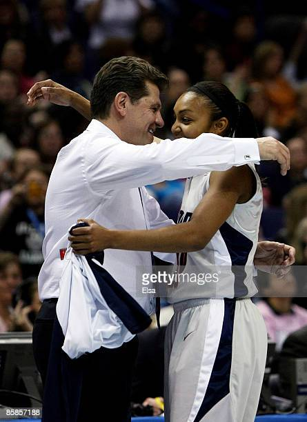 Head coach Geno Auriemma of the Connecticut Huskies congratulates Renee Montgomery after she was pulled from the game in the second half against the...