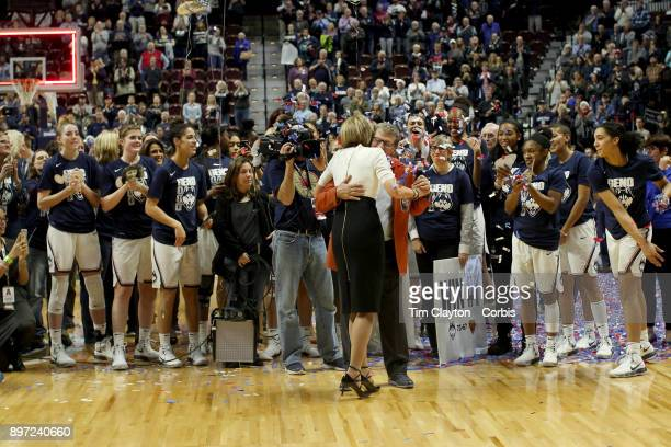 Head coach Geno Auriemma of the UConn Huskies and assistant coach Chris Daley embrace after recorded their 1000th win as head coach and assistant...