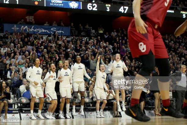 Head coach Geno Auriemma of the UConn Huskies on the sideline while recording his 1000th win as head coach of the team as the Uconn team celebrate a...