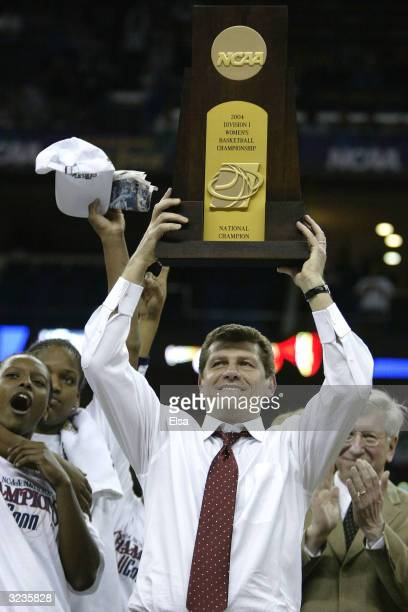 Head coach Geno Auriemma of the University of Connecticut Huskies holds the NCAA National Championship trophy after defeating the Tennessee Lady Vols...