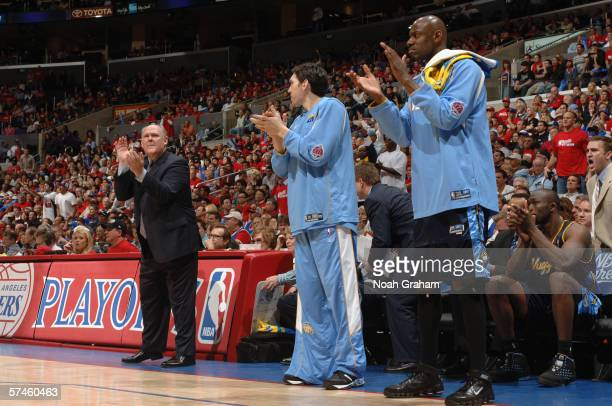 Head coach George Karl Eduardo Najera and Francisco Elson of the Denver Nuggets cheer from the bench against the Los Angeles Clippers in game one of...