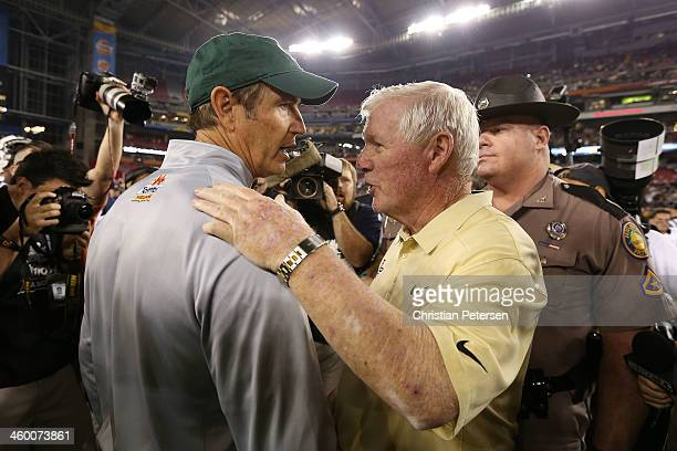 Head coach George O'Leary of the UCF Knights shakes hands with head coach Art Briles of the Baylor Bears after the Knights defeated the Bears 52 to...