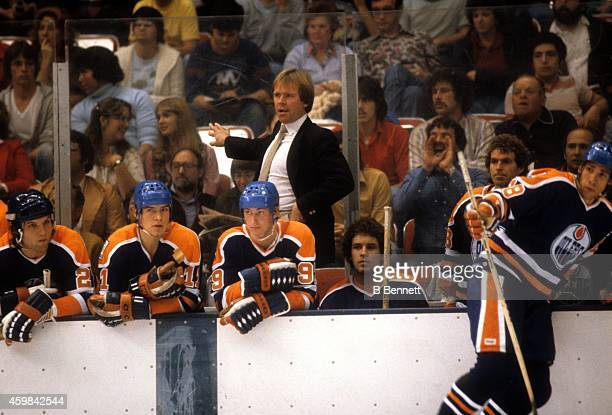 Head coach Glen Sather Mark Messier and Wayne Gretzky of the Edmonton Oilers look on from the bench during an NHL game against the New York Islanders...
