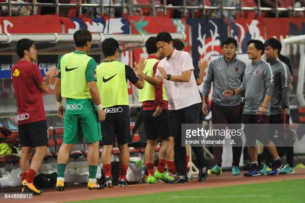 Head coach Go Oiwa of Kashima Antlers high fives with Mitsuo Ogasawara after their 10 victory in the JLeague J1 match between Kashima Antlers and...