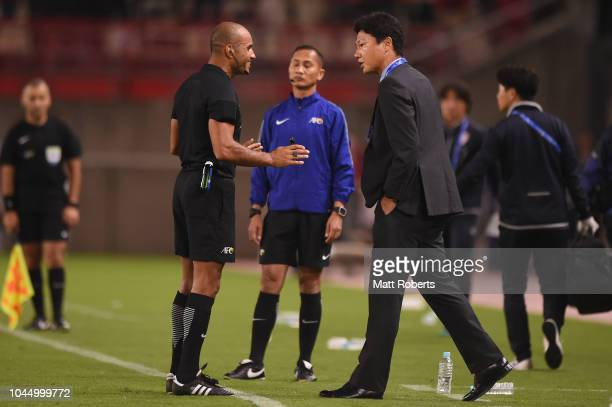 Head coach Go Oiwa of Kashima Antlers speaks with referee Nawaf Shukralla during the AFC Champions League semi final first leg match between Kashima...