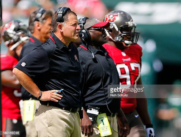 Head coach Greg Schiano left of the Tampa Bay Buccaneers looks on during a game against the New York Jets at MetLife Stadium on September 8 2013 in...