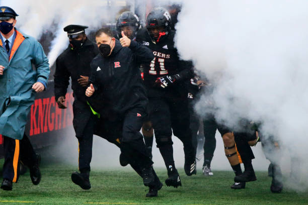 Head coach Greg Schiano of the Rutgers Scarlet Knights runs onto the field before the game against the Penn State Nittany Lions at SHI Stadium on...